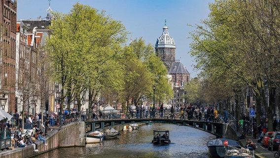 Blick entlang eines Kanals in Amsterdam mit Häusern und vielen Menschen auf der Straße © picture alliance / NurPhoto Foto: Nicolas Economou