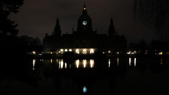 Am Rathaus in Hannover wird während der Earth Hour 2016 das Licht ausgeschaltet, nur Fackeln und die Uhr leuchten. © picture alliance/dpa Foto: Peter Steffen