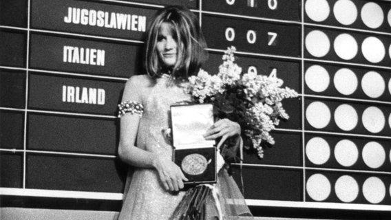 Sandie Shaw posiert nach ihrem Sieg im Grand Prix EUrovision 1967 vor der Anzeigetafel. © UPI