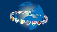 Die Länder-Fähnchen-Herzen der Eurovisionslogi laufen um eine Weltkugel.  Foto: Jonas Ockelmann
