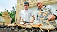 Zwei Männer grillen Bratwürste in der aserbeidschanischen Botschaft. © NDR Fotograf: Rolf Klatt