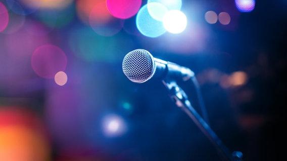 Ein Mikrofon auf einer Bühne zwischen bunten Lichtern. © fotolia.com Foto: Saon168, Andrey Armyagov