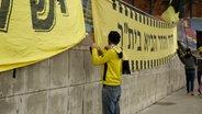 Ein Fan bringt die Flagge des Vereins Beitar Nordia im Stadion an