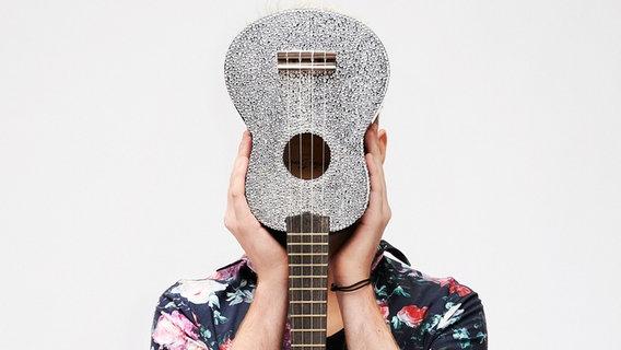 Jendrik Sigwart, Deutschlands Kandidat für den Eurovision Song Contest 2021, hält seine Ukulele vor sein Gesicht. © NDR
