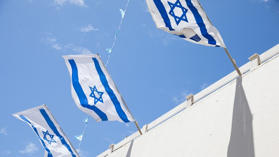 Fahnen wehen von einem Hausdach in Tel Aviv. © NDR Foto: Claudia Timmann
