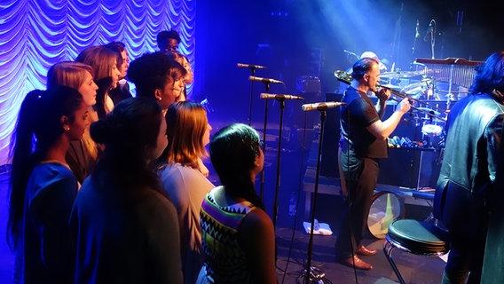 Ein Gospelchor steht auf der Bühne im Theater am Aegi. © NDR Foto: Marie Löwenstein