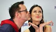 Ein Mann wirft einen Kussmund in Richtung Wange einer Frau. © NDR 2
