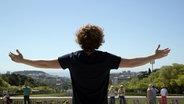 Michael Schulte bereitet beide Arme aus und schaut auf Lissabon. © NDR / Rolf Klatt Foto: Rolf Klatt