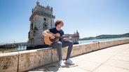 Michael Schulte spielt Gitarre am Turm vom Belém in Lissabon. © NDR / Rolf Klatt Foto: Rolf Klatt