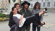 The Makemakes tragen Ann Sophie auf einem Platz in Salzburg auf Händen