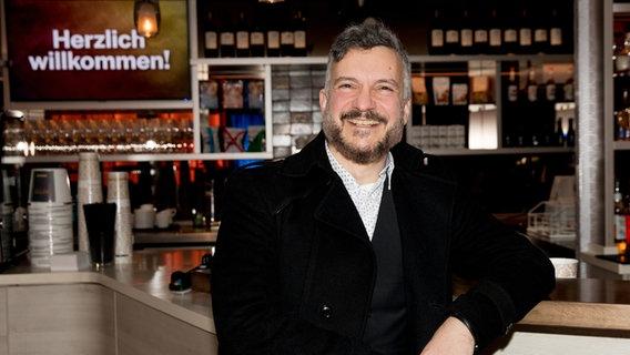 Irving Wolther steht an einer Bar und lacht in die Kamera.  Foto: Claudia Timmann