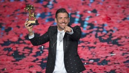 Francesco Gabbani mit seiner Sieges-Trophäe beim Sanremo Festival 2017 © Picture-Alliance / Pacific Press Foto: Pamela Rovaris