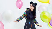 Sängerin Jamie-Lee Kriewitz steht mit buntem Kleid und Plüschohren inmitten von Luftballons. © Universal Music