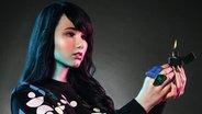 Sängerin Jamie-Lee Kriewitz ist gestylt wie eine Puppe und schaut auf ein Feuerzeug in ihrer Hand. © Universal Music