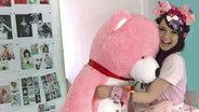 Jamie-Lee hat einen riesigen rosa Teddy im Arm.