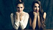 Die Musikerinnen Josepha und Cosima von Joco stützen ihre Ellenbogen auf einem Tisch ab und starren in die Kamera. © Sony Music