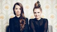 Die Musikerinnen Cosima und Josepha von Joco sitzen auf einem Sofa und starren in die Kamera. © Sony Music