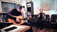 Produzent Roland Spremberg (li) und Levina sitzen im Tonstudio und machen Musik