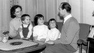 Paola Felix sitzt 1959 zusammen mit ihren Eltern und zwei Geschwistern auf einem Sofa. Alle gucken den Vater an. © Paola