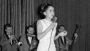 Die Sängerin Paola steht 1964 auf einer Bühne und singt. Hinter ihr die Begleitband. © Paola