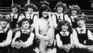 Die Sängerin Paola Felix sitzt 1980 in der ZDF Hitparade auf einer Treppe, umringt von Mädchen mit Zöpfen, die alle gleich angezogen sind. © Paola