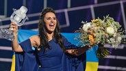 Jamala aus der Ukraine hält den ESC-Pokal und eine Flagge in die Höhe. © dpa - Bildfunk Fotograf: Maja Suslin