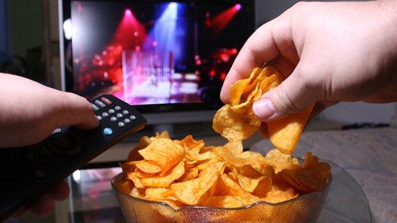 Eine Hand greift vor einem Fernseher in eine Chipsschüssel. © Fotolia.com_13182749_S, © Fabian Rothe Foto: © Fabian Rothe