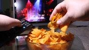 Eine Hand greift vor einem Fernseher in eine Chipsschüssel. © Fotolia.com_13182749_S, © Fabian Rothe Fotograf: © Fabian Rothe