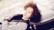Der Sänger und Songwriter Michael Schulte lehnt mit dem Kopf auf einem Gitarrenkasten.  Foto: Sven Sindt