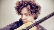 Der Sänger und Songwriter Michael Schulte hält eine Gitarre im Arm.  Foto: Sven Sindt