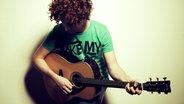 Der Sänger Michael Schulte spielt Gitarre  Foto: Sven Sindt