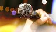 Mikrofon in einer Hand. © fotolia Fotograf: carloscastilla