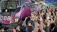 """Ein Zug mit dem Logo des ESC 2015 """"Building Bridges"""" fährt im Bahnhof ein und wird von Hunderten jubelnder Fans begrüßt. © ORF"""
