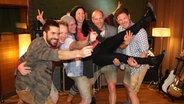 Die fünf Mitglieder der Band VoXXclub heben Choreografin Nici Grandison hoch und lachen in die Kamera. © Marcel Stober Fotograf: Marcel Stober